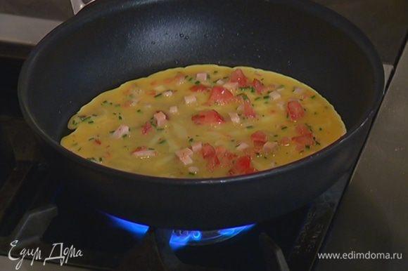 В тяжелой сковороде разогреть 1 ст. ложку оливкового масла и тонким слоем влить половину яичной смеси.