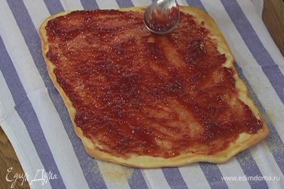 Выложить на полотенце с сахаром пласт из теста, снять с него бумагу для выпечки и, пока он горячий, смазать тонким слоем малинового варенья.