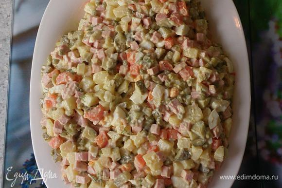 Готовим салат как обычно. Отвариваем картофель, морковь, яйца, даем остыть. Тем временем нарезаем кубиками колбасу, огурцы; затем картофель, морковь, яйца. Я добавляю немного огуречного рассола. Солим, перчим по вкусу. Добавляем рубленый укроп, зеленый горошек. Заправляем майонезом. Выкладываем на сервировочную тарелку в форме овала, сверху немного уже.