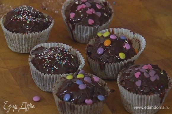 Готовые капкейки полить шоколадной глазурью и украсить сахарными бусинками и сердечками.
