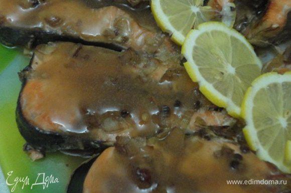 Часть маринада, примерно 1/2 стакана, слейте в отдельную посуду (желательно без овощей и пряностей), а оставшуюся часть (при необходимости) разбавьте ½ стакана воды. Рыбное филе залейте разведенным маринадом и тушите 20-25 минут в нагретой до 200-220 градусов духовке. Оставшийся маринад доведите до кипения, добавьте разведенный небольшим количеством воды крахмал и проварите до загустения. Перед подачей уложите филе на подогретую тарелку, полейте соусом и оформите лимоном и зеленью.