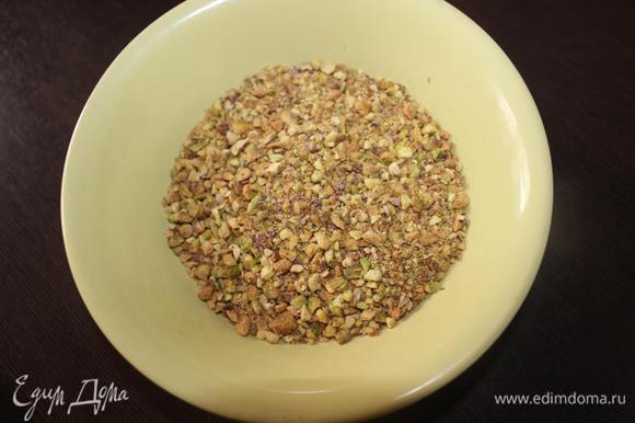 Заранее подготовим орехи. Если у вас есть очищенные несоленые, то просто измельчаете их (не совсем в муку, а чтобы они чувствовались в выпечке). Если же, как в моем случае, фисташки соленые и неочищенные, то чистим орешки от скорлупы и промываем в холодной воде. Подсушиваем на бумажном полотенце, а затем на горячей сковороде без масла. А затем измельчаем. Для получения 100 граммов мне понадобилось где-то 210-220 грамм неочищенных орехов. Для бисквита отмеряем 90 грамм, а остальные пойдут на украшение готового торта.