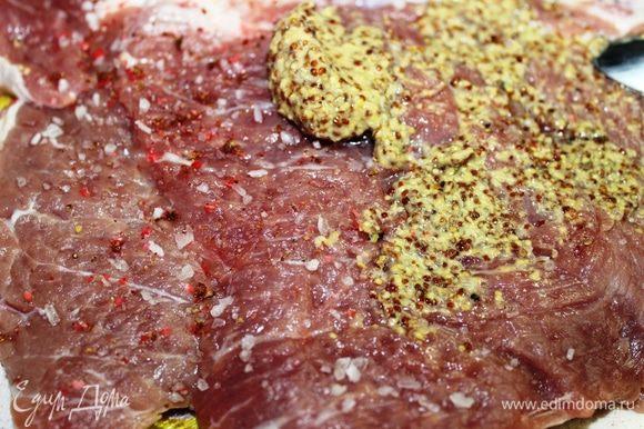 Посыпать мясо крупной солью, свежемолотым розовым перцем и смазать горчицей.