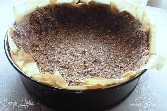 Форму (у меня 20 см) выстелить бумагой для выпечки. Выложить сверху смесь из орехов и семечек, но не всю. Оставить 3-4 ст. л. Сделать бортики.