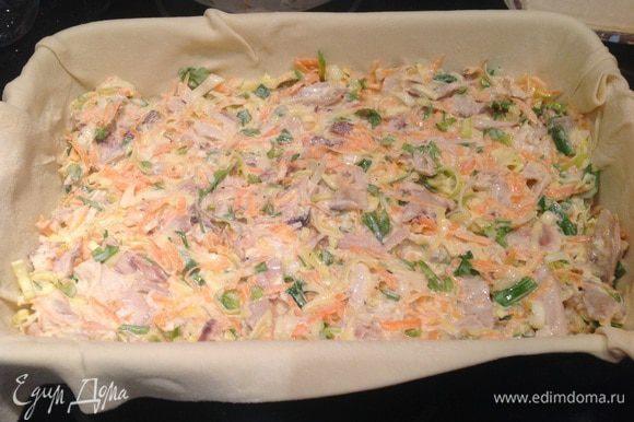 Выложите тесто в смазанную маслом форму, так чтобы края свисали и выложите начинку.