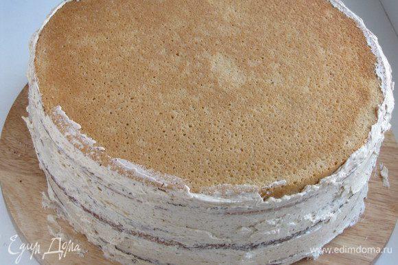 Положить один корж на другой, накрыть третьим бисквитным коржом, промазать бока торта.