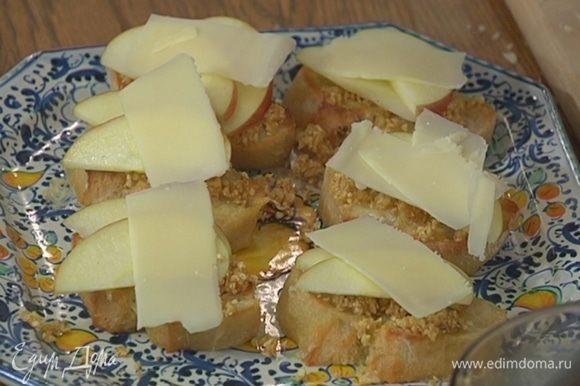 Горячую брускетту смазать орехово-инжирной пастой, на каждый кусочек выложить по паре долек яблока, а сверху — ломтик сыра.