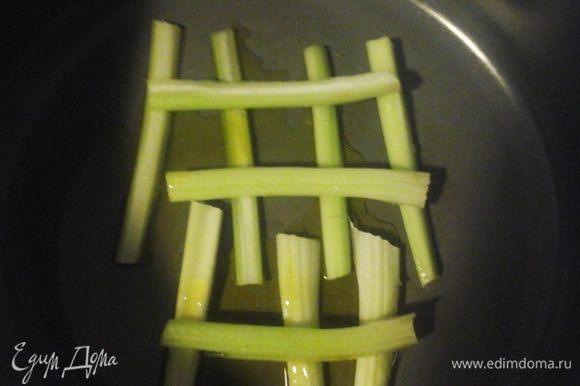Разрезать сельдерей по длине и выложить на дно кастрюли (это придаст вкус и послужит защите от пригорания трески).