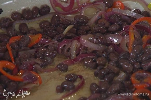 В сковороду с луком и чесноком добавить нарезанный чили, фасоль, все перемешать и прогреть.