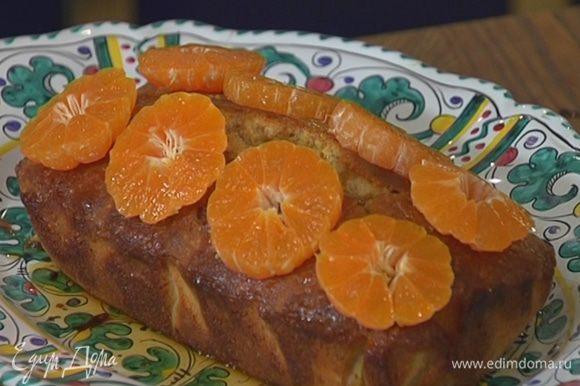 Оставшиеся мандарины почистить, нарезать поперек кружками и выложить на кекс.