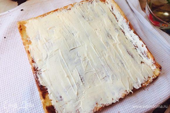 Развернуть рулет, смазать бисквит сиропом. Затем, тонким слоем распределить светлый крем по поверхности коржа.