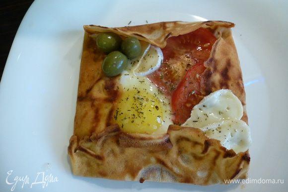 """Блинчик переворачиваем. В """"тарелочку"""" выкладываем пластики помидора, пластики сыра """"Бри"""", разбиваем яйцо, солим, посыпаем итальянскими травами. Закрываем сковороду крышкой и жарим на среднем огне до необходимой готовности яйца. Готовый блинчик украшаем оливками и сбрызгиваем оливковым маслом. Мужской завтрак готов! Приятного аппетита!"""