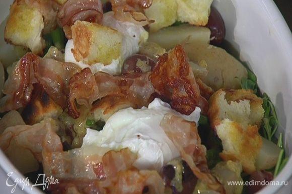 На салат поместить яйца пашот, посыпать все хлебными крутонами, украсить обжаренным беконом и сбрызнуть оливковым маслом Extra Virgin.