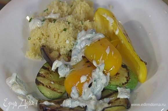Обжаренные овощи выложить на тарелку с кускусом и полить соусом.
