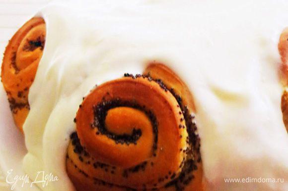 Оставляем булочки в форме на 5 минут, затем перекладываем на блюдо и обильно поливаем сливочным кремом.