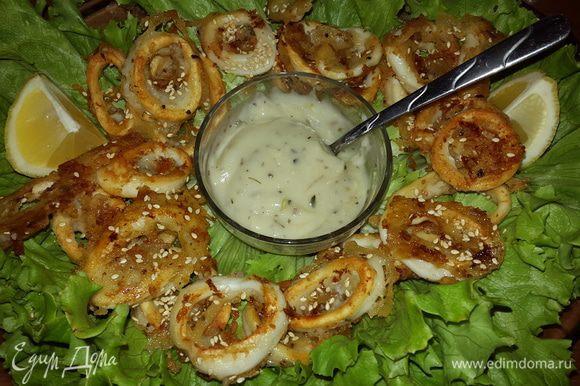 На большое блюдо выкладываем листья салата, по центру ставим соус, а вокруг выкладываем кольца кальмаров, подаем к столу. Приятного аппетита!