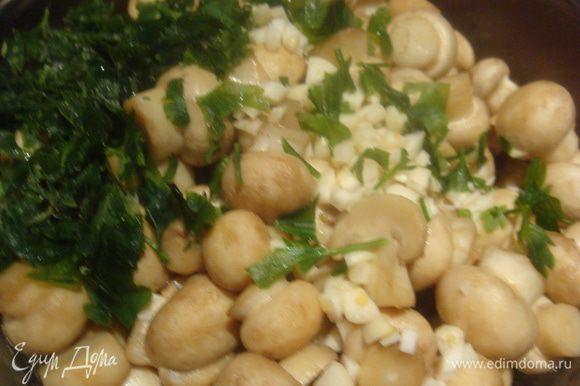 Грибы выложить в глубокую тарелку или кастрюльку, в которой мы их будем заправлять. В горячие грибы добавить порезанный чеснок, зелень.
