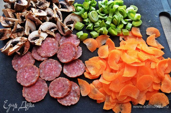 Начинаем подготовку салатика. Шампиньоны разрежем на четверти, порей на кольца, морковку на полукруги слайсами строгаем, салями - тонкими кружками.