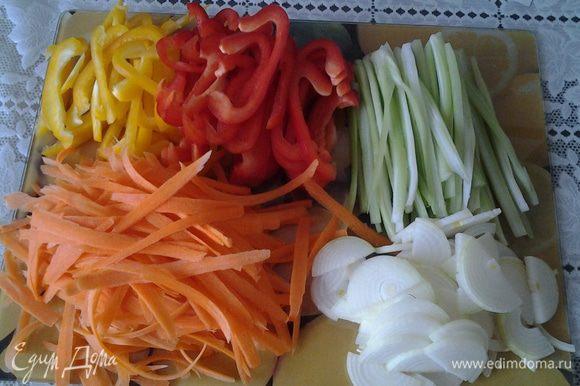 Приготовить овощи: помыть, очистить. Сельдерей разрезать пополам, затем каждую половинку разрезать на тонкие полоски. Морковь нарезать тонкими пластинками при помощи овощерезки. Перец разрезать пополам, затем каждую половинку тонкими полосками. Лук порезать полукольцами.