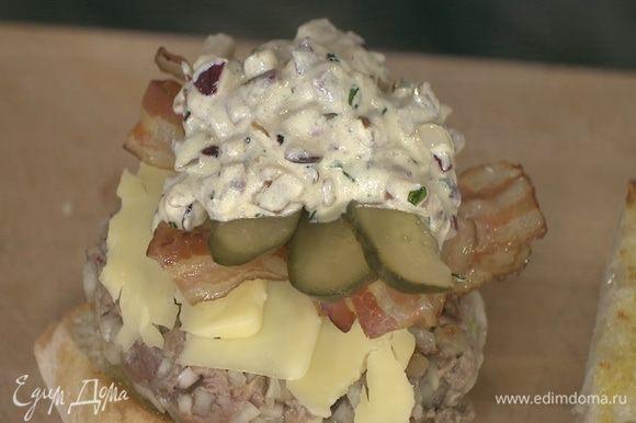 Один кусок хлеба смазать дижонским соусом, выложить на него котлету, сыр, бекон, полоски огурца, смазать все соусом и накрыть вторым куском хлеба.