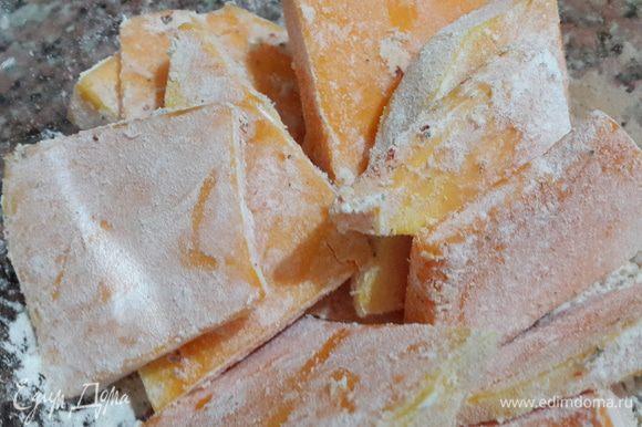 Тыкву нарезаем пластиками толщиной не более 0,5 см. Солим, посыпаем перцем, сушеным базиликом и мукой. Перемешиваем, равномерно распределяя по кусочкам тыквы. Отставляем в сторону на 7-10 минут.