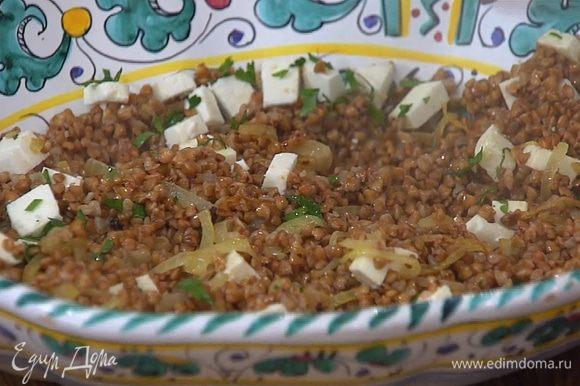 Гречку с луком выложить в глубокое блюдо, посыпать большей частью сыра и петрушки и посолить.
