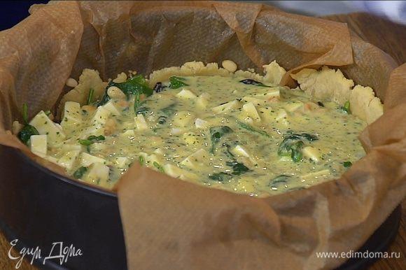Вынуть подпеченный корж из духовки, удалить бумагу с горохом, на тесто выложить шпинат с луком, сверху вылить яичную массу с козьим сыром. Выпекать пирог еще 25–30 минут.