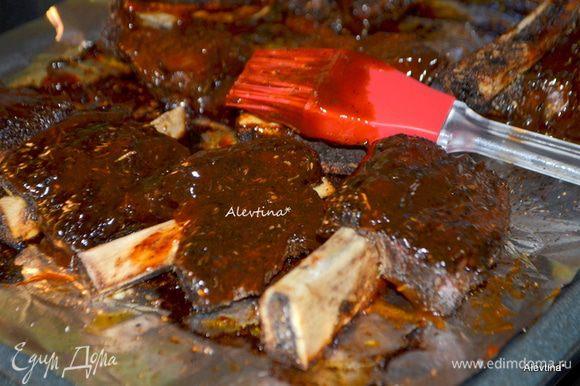 По истечении времени смазать ребра со всех сторон в готовом купленном или домашнего приготовления барбекю соусе и вернуть в духовку на 30 мин.