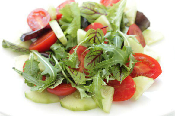 На тарелки выложить горсти руколы, мангольда, кружочки огурца , дольки помидоров и тонко порезанный лук.