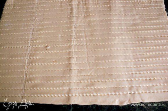 Готовое слоеное тесто разморозить, раскатать в пласт толщиной 5 мм и порезать на полоски шириной 10-15 мм.