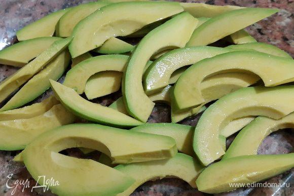 Авокадо моем, чистим, удаляем косточку, режем ломтиками толщиной примерно 0,7 см и сбрызгиваем соком половины лимона.
