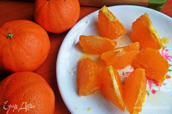 С мандарина срезать ножом вначале кожицу на манер яблока, а потом нарезать на сегменты, чтобы вся белая мякоть осталась на шкурке. Разрезаем пополам каждую дольку.