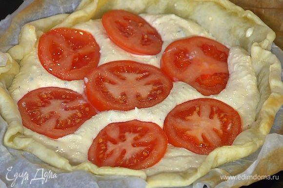 На подпеченный корж равномерно выложить творожную начинку, сверху разложить кружки помидора и немного вдавить их в творог.