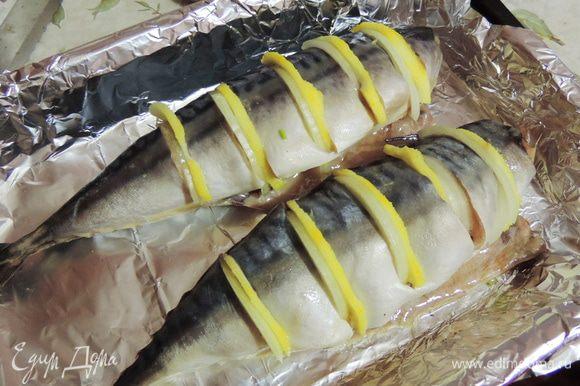 Затем нарезаем рыбку на порционные кусочки, не прорезая полностью. В полученные надрезы вкладываем тоненькие полукольца лука и лимона.
