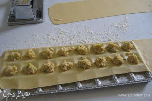 Раскатать тесто с помощью машинки для пасты или скалкой на длинные прямоугольники. Положить один пласт в форму для равиоли, посыпанную мукой. Прижмите тесто так, чтобы сформировались небольшие лунки для начинки.