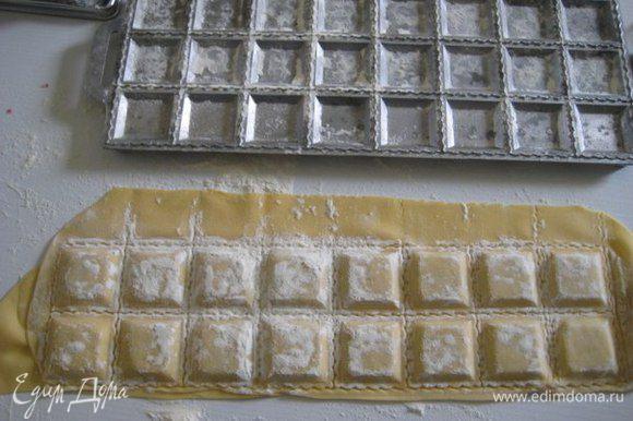 Наполните лунки начинкой, смажьте слегка тесто вокруг начинки водой и накройте вторым пластом теста. Покатать сверху скалкой, чтобы сформировались равиоли.