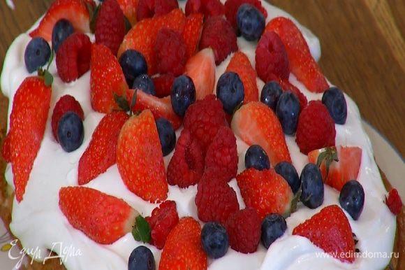 На остывший пирог выложить взбитые сливки, разровнять и украсить сверху свежими ягодами.