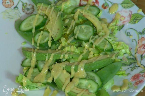 На блюдо выложить салат, сельдерей, огурец, стручки горошка и авокадо, сбрызнуть все заправкой, посолить и поперчить.