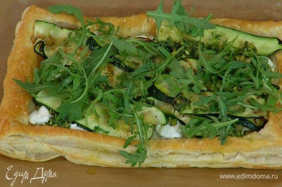 Готовый пирог сбрызнуть оставшимся оливковым маслом и украсить руколой.