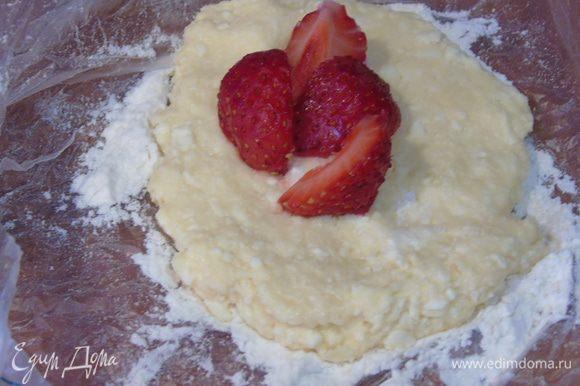 Творожное тесто разделить на 6-8 частей, каждую часть размять в лепешечку, в середину положить нарезанную клубнику.