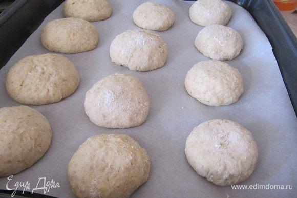 Рабочую поверхность посыпать мукой, выложить тесто, разделить на 12 равных частей, сформируйте булочки. Противень выстелить пекарской бумагой, выложить булочки, оставить на полчаса.