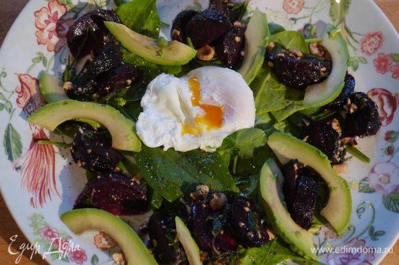 На шпинат выложить свеклу с орехами и авокадо, сверху поместить яйцо пашот.