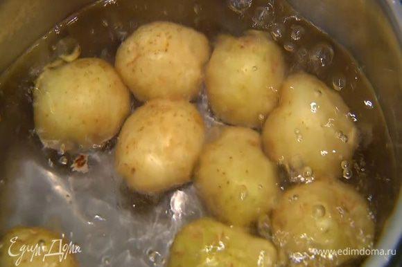 Картофель вымыть и, не очищая, отварить в кипящей соленой воде до готовности, затем воду слить.