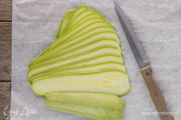 Кабачки помыть и нарезать тонкими ломтиками вдоль.
