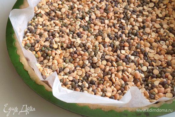 Закрыть тесто листом бумаги и насыпать сухую фасоль или горох. Поставить основу в духовку и выпекать 15 минут при 160 град.