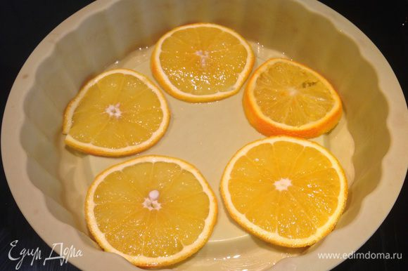 Один апельсин нарежьте кружочками и выложите на дно формы. Второй апельсин очистите и нарежьте небольшими ломтиками.