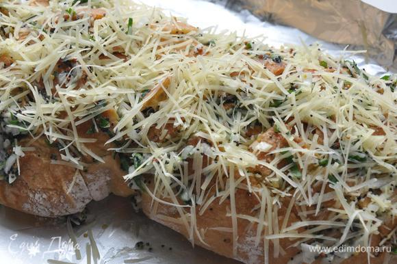 Сыр мелко натереть и разложить в разрезы. Накрыть чабатту фольгой, плотно закрыть. Запекать на решетке гриля 10-12 минут до расплавления сыра.