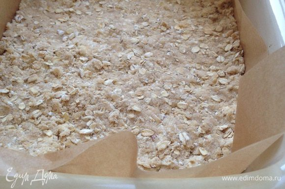 Форму застелить бумагой для выпечки так, чтобы края бумаги свисали на 2-3 см. Выложить на дно формы 2/3 мучной крошки. Равномерно распределить по дну и слегка придавить руками.