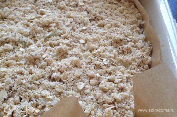 Поверх крошки выложить яблоки (можно присыпать корицей). Присыпать яблоки оставшейся крошкой. Выпекать в предварительно разогретой духовке до 180°C 30-35 минут.