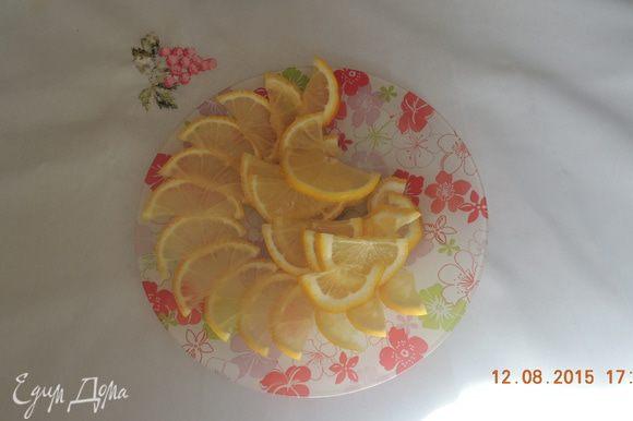 Нарезать лимоны тонкими ломтиками.